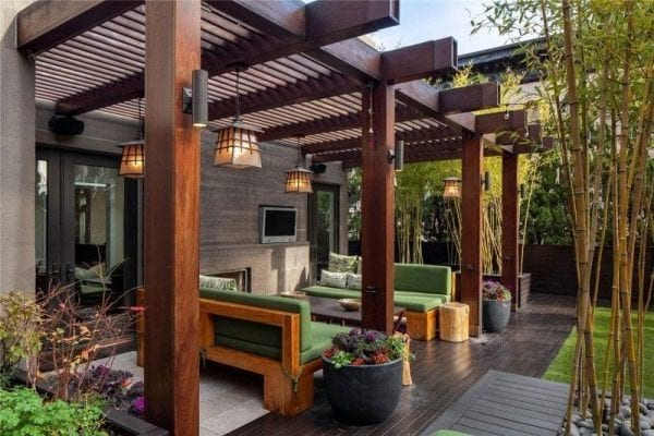 a stunning pergola shading green couches in the backyard