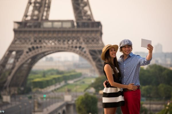 a couple taking a picture in front of the eiffel tower