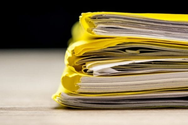 paper work inserted inside a yellow folder sitting on a table