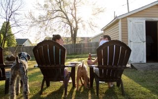 a couple relaxing in their backyard with having a conversation
