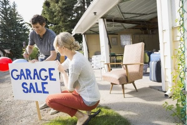 a couple putting up a garage sale sign