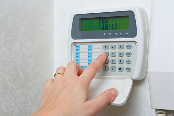 a hand pointing at a security alarm system