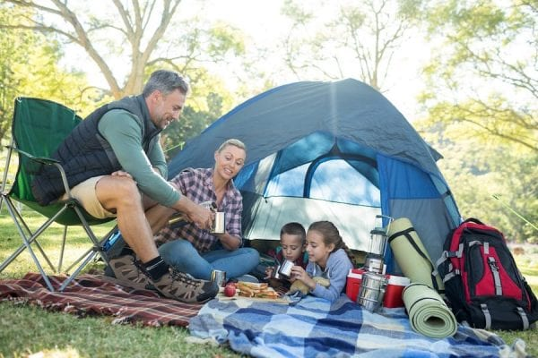 a family having snacks and coffee outside the tent