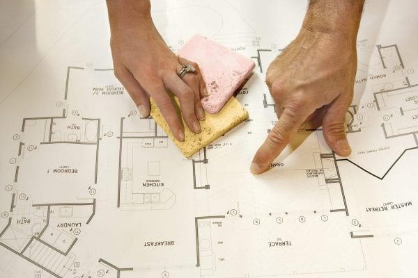 a couple pointing at a floor plan