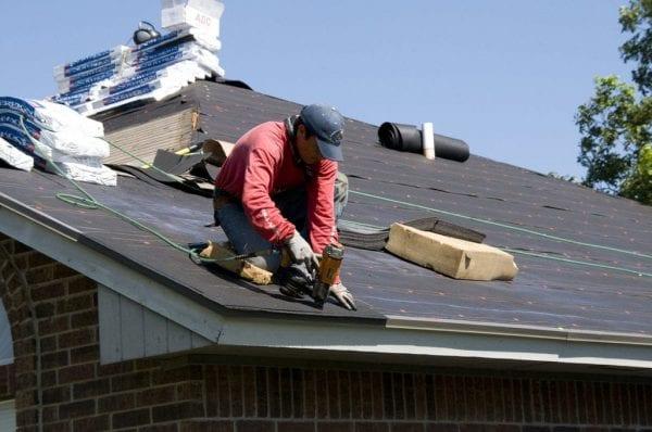 a handyman drilling shingles onto a a roof