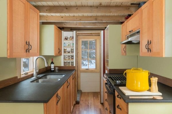 a spacious kitchen with storage cabinets in a tiny home