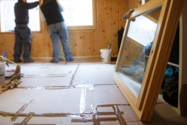 two builders installing a window