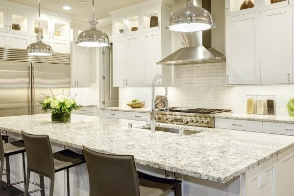 White kitchen design featuring large bar style kitchen island with granite countertop illuminated by modern pendant lights