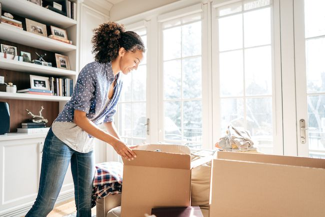 A woman happily unpacking her things in her new home