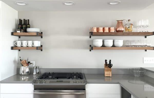 A modern kitchen with an organized open shelf