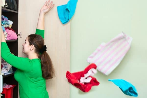 A woman tossing clothes out of her closet