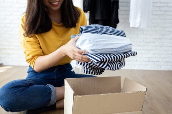 A smiling woman putting clothes inside a cardboard box