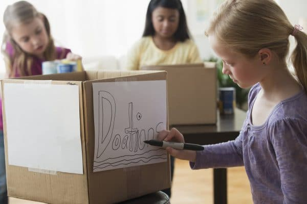 A girl writing 'donations' on a cardboard box with a pen