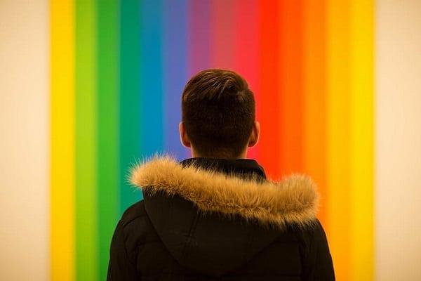 A man facing a rainbow-coloured wall