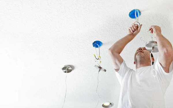 A man in a white shirt isntalling a light bulb on the cieling