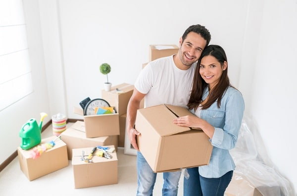 A couple happily carrying a cardboard box in their new apartment