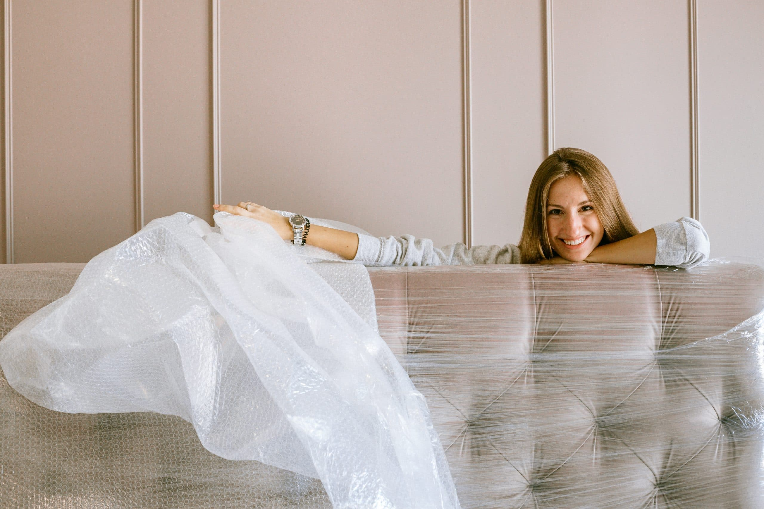 A woman leaning on a couch covered in plastic