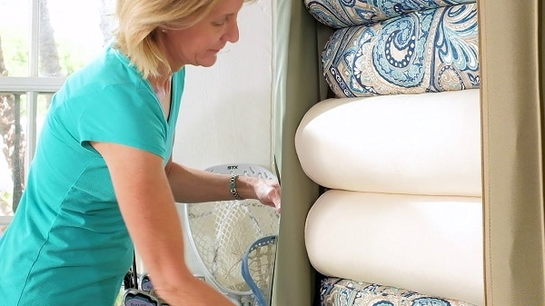 A woman storing cushion in a storage box