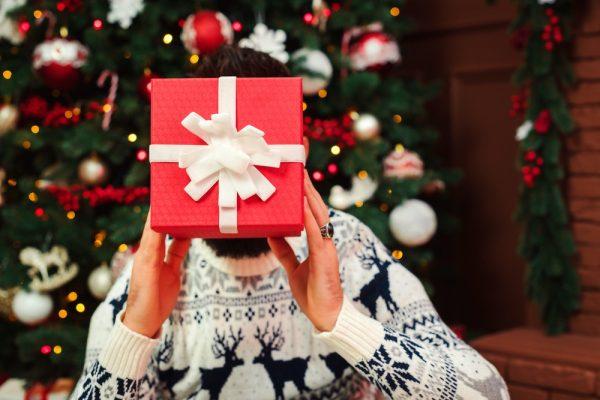 A person hiding behind a gift box