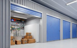 Opened storage unit door with cardboard boxes